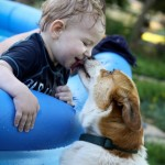 My son enjoying a kiddie pool, and some puppy kisses!